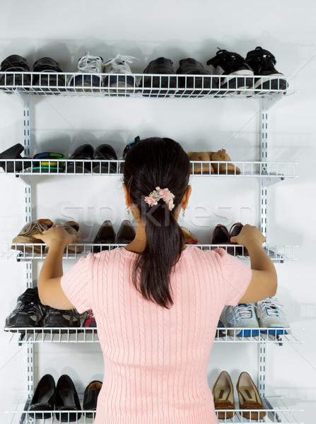Woman selecting footwear from the shoe rack mounted on wall Stock photo © tab62