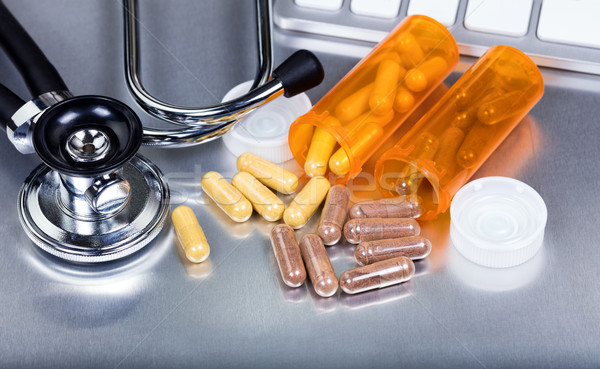Capsules and medicine bottles plus medical equipment on stainles Stock photo © tab62