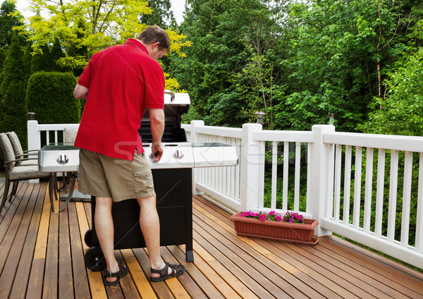 Mature man turning on barbecu grill while outside on open deck  Stock photo © tab62