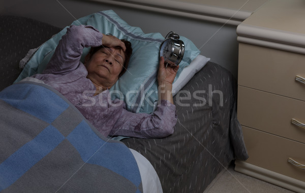 Restless senior woman with migraine during nighttime while in be Stock photo © tab62