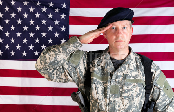Veteran solider saluting with USA flag in background while armed Stock photo © tab62