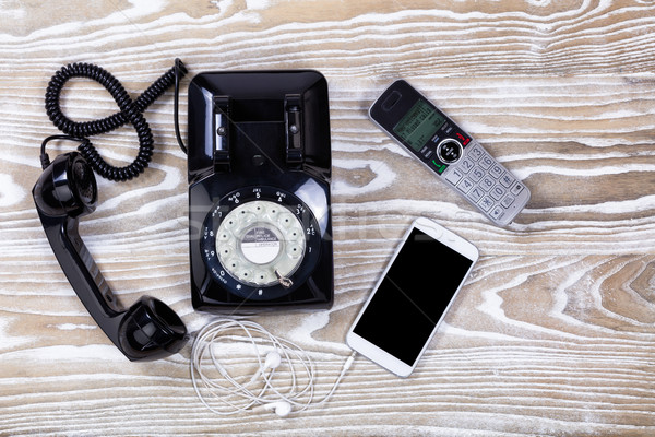 Retro telephone with modern communication devices on faded wood  Stock photo © tab62