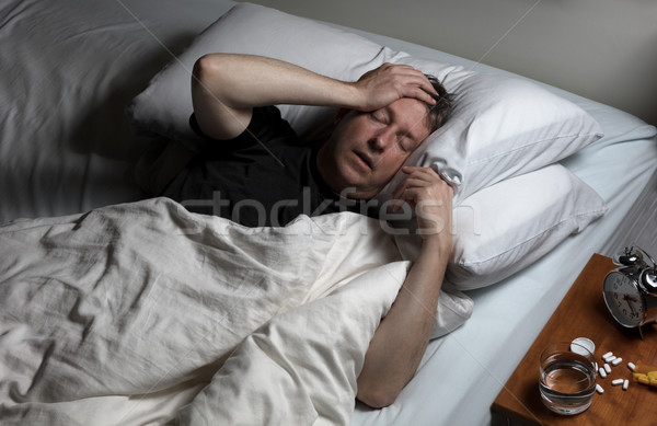 Stock photo: Mature man in physical pain while trying to fall asleep
