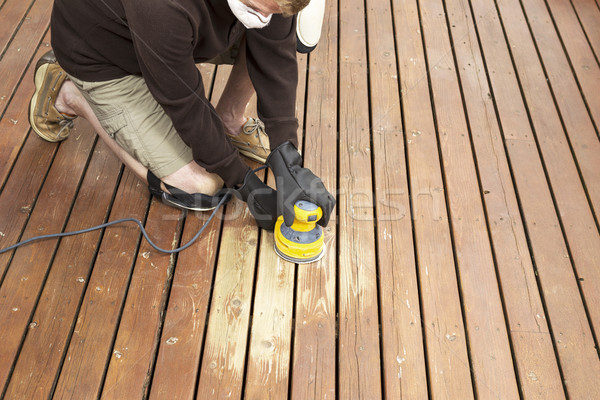 Mature man performing maintenance on home wooden deck  Stock photo © tab62