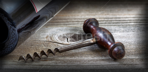 Old corkscrew and wine bottle on aged wood with vignette border  Stock photo © tab62