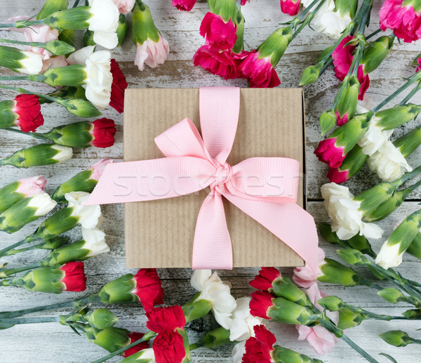 Colorful carnation flowers around gift box on white weathered wo Stock photo © tab62