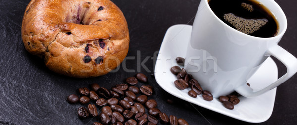 Roasted coffee beans with drink and bagel in background on slate Stock photo © tab62