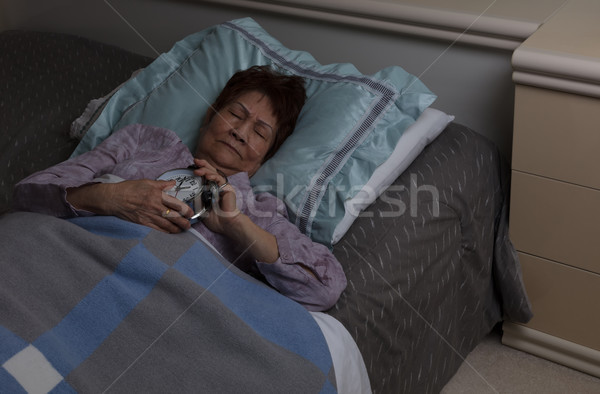 senior woman holding her alarm during sleepless night while in b Stock photo © tab62
