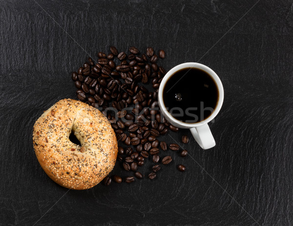 Dark coffee and bagel with roasted beans on natural slate stone  Stock photo © tab62