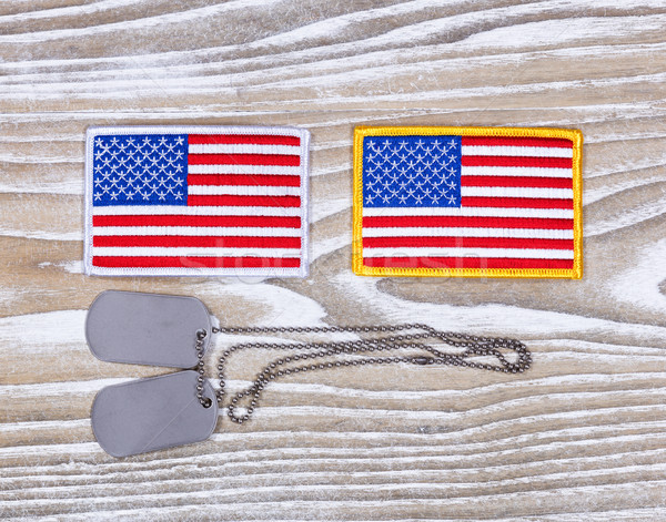 Small USA flag patches and military ID tags on rustic white wood Stock photo © tab62