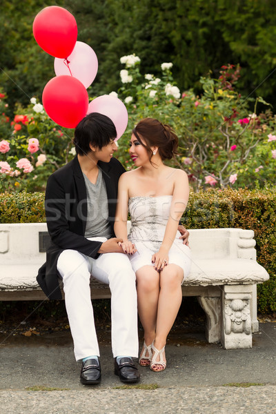 Young Adult Couple Sitting down on Bench in front of Rose Garden Stock photo © tab62