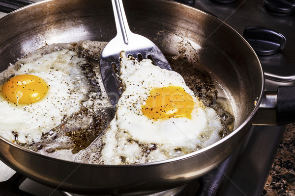 Eggs cooked with bacon grease in pan  Stock photo © tab62