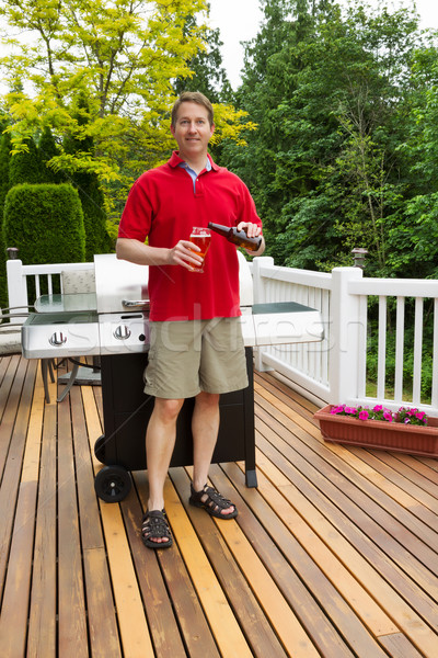Mature man pouring beer into glass while outdoors on open patio  Stock photo © tab62