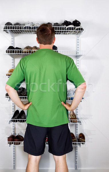 Man selecting footwear from the shoe rack mounted on wall Stock photo © tab62
