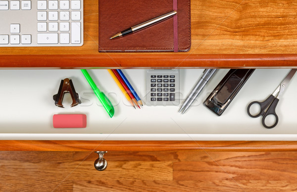 Organized desktop and open drawer with wooden floor underneath Stock photo © tab62