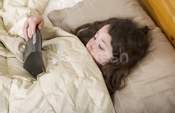 Young girl over sleeps and looks at alarm clock in surprise  Stock photo © tab62