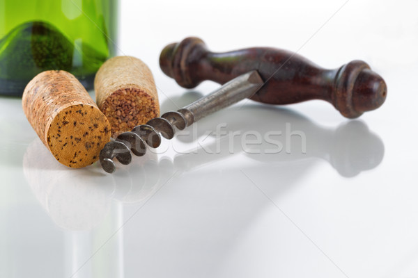 Old corkscrew with corks and wine bottle on glass table Stock photo © tab62