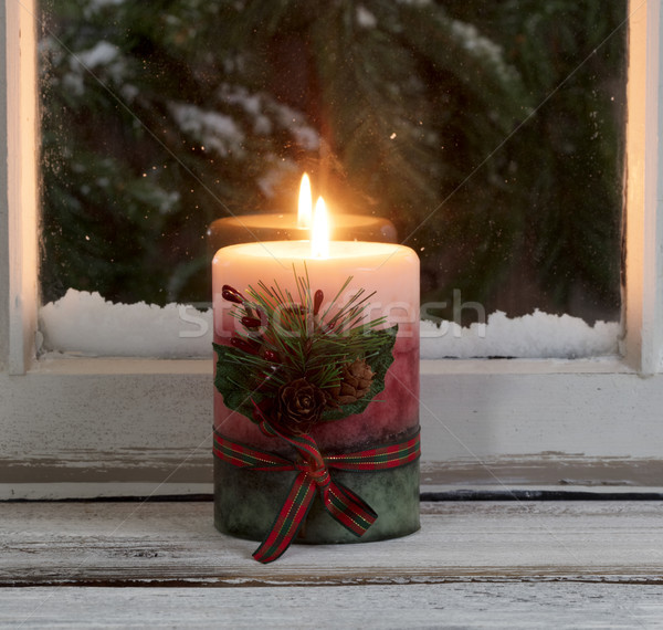 Christmas candle glowing on window sill with snowy evergreen bra Stock photo © tab62