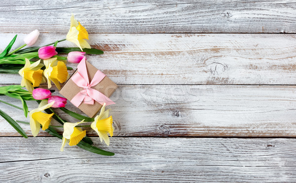 Yellow daffodils and pink tulips with gift box on white weathere Stock photo © tab62