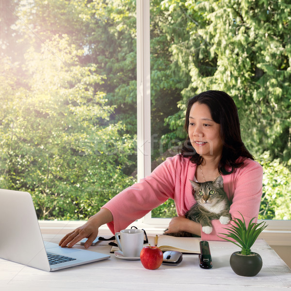 woman holding her family pet cat while working from home  Stock photo © tab62
