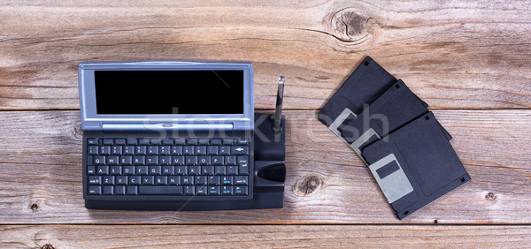 Vintage handheld computer and data disks on rustic wooden boards Stock photo © tab62