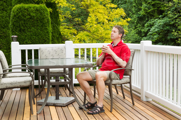 Mature man resting in chair on outdoor patio with cup of coffee  Stock photo © tab62