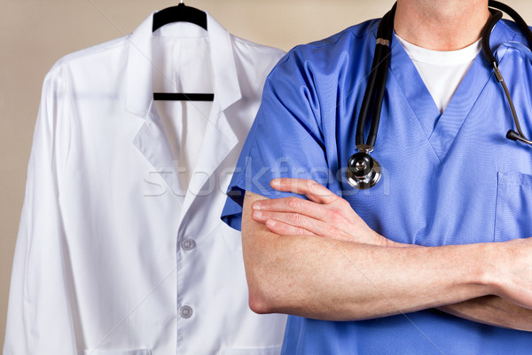 Medical doctor wearing blue scrubs with white consultation coat  Stock photo © tab62
