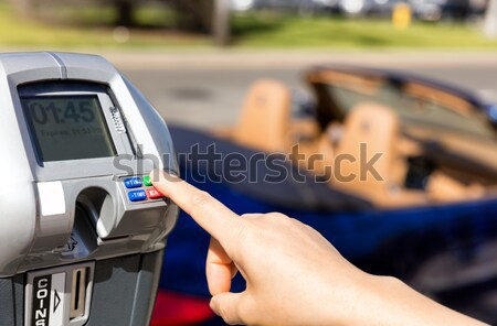 Hand putting credit card into parking meter with convertible car Stock photo © tab62