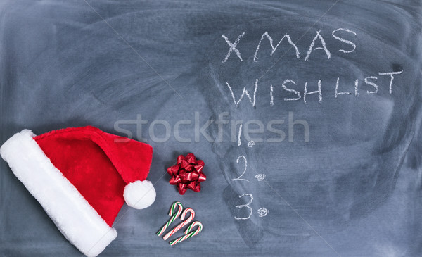 Erased black chalkboard with Santa cap and candy canes plus text Stock photo © tab62