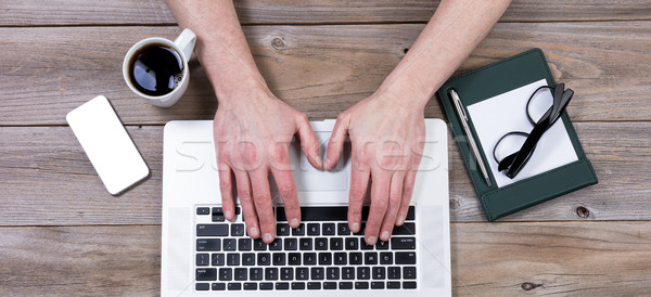 Top view of working desktop with hands on laptop keyboard with o Stock photo © tab62