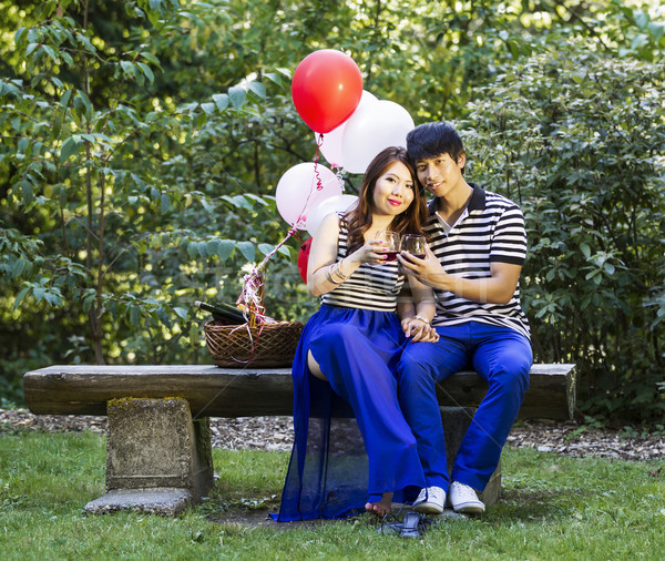 Stock photo: Young Lovers Sharing a Moment of Drinking Red Win while Outdoors