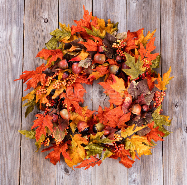 Wreath made of autumn leaves and acorns on rustic wooden boards Stock photo © tab62