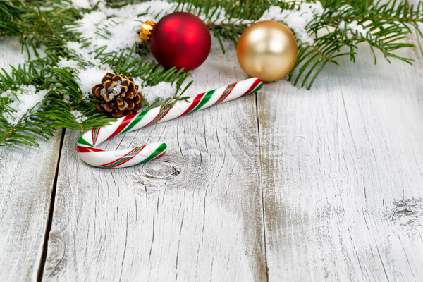 Candy cane with snow covered fir branches and ornaments on rusti Stock photo © tab62