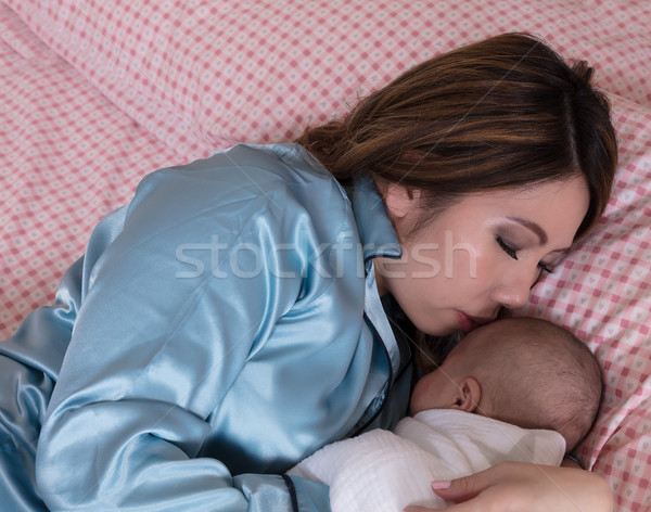 Mom closely holding her infant son while sleeping in bed  Stock photo © tab62