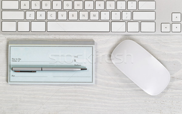 Blank checkbook on white desktop with pen and mouse  Stock photo © tab62