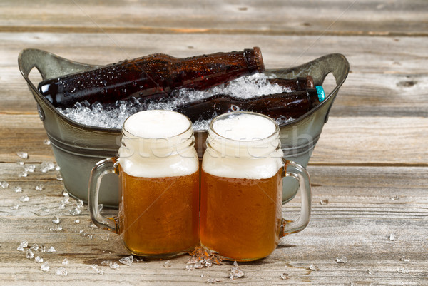 Two pints of fresh cold beer in front of bucket filled with ice  Stock photo © tab62