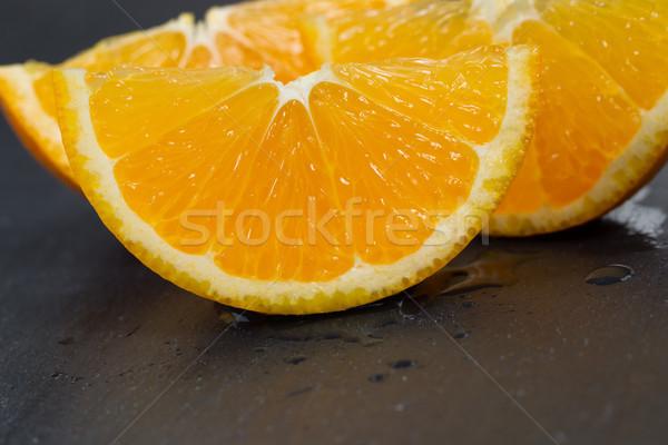Freshly sliced orange fruit on black slate stone background  Stock photo © tab62