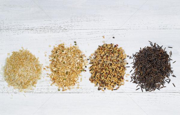 Varieties of Rice in piles on top of White Wood Stock photo © tab62