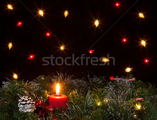 Christmas candle burning with evergreen and dark background with Stock photo © tab62