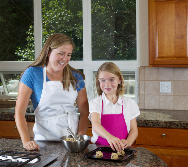 Mother teaching her daughter how to make cookies from raw dough  Stock photo © tab62