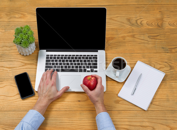 Male hand holding apple while using laptop computer  Stock photo © tab62