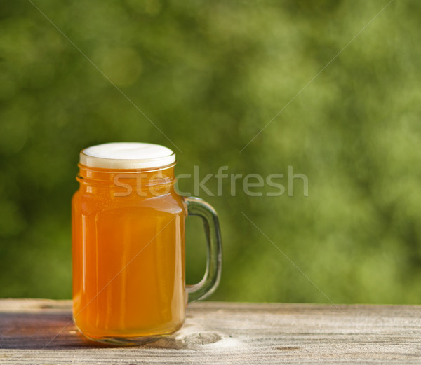 Full pint of golden beer ready to drink outdoors Stock photo © tab62