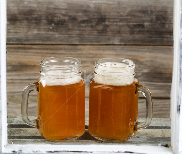 Window view of two pints of fresh cold beer on top of wooden cra Stock photo © tab62