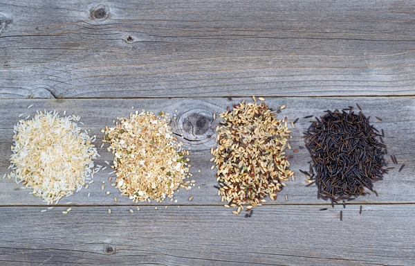 Varieties of Rice in piles on top of rustic wood  Stock photo © tab62