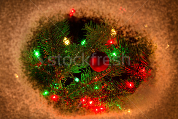 Red ornament hanging on fir tree branch with lights and surround Stock photo © tab62
