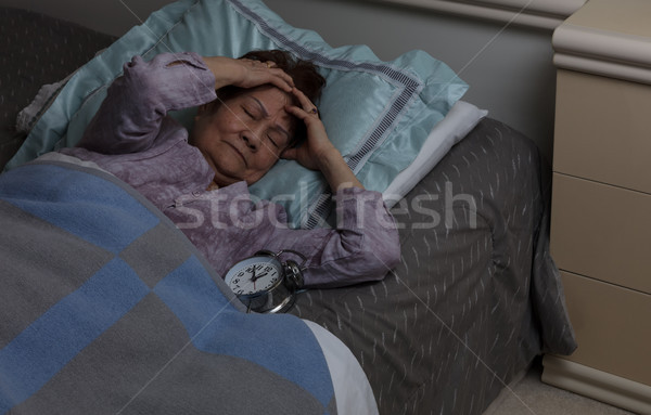 senior woman with headache during nighttime while in bed Stock photo © tab62