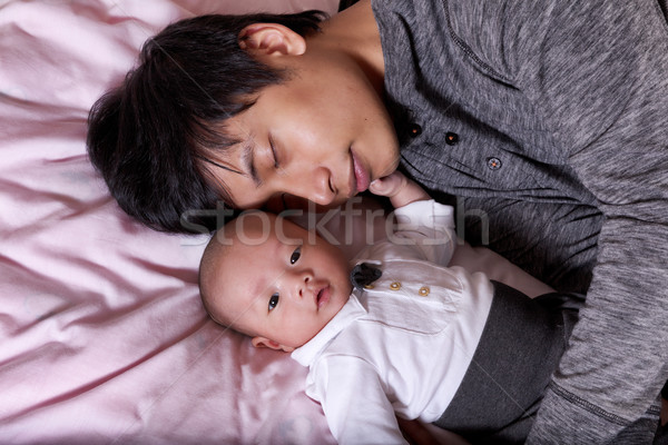 Restless infant baby boy with his sleeping father Stock photo © tab62