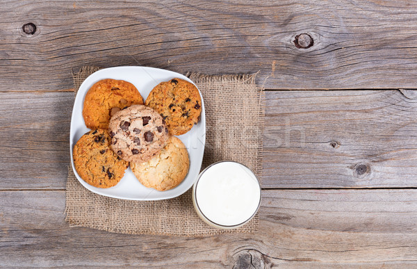 Variety of baked cookies in napkin and glass of milk on rustic w Stock photo © tab62