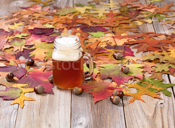 Freshly poured beer with autumn foliage and acorns on rustic woo Stock photo © tab62