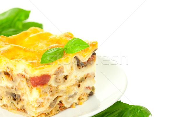 Portion of Classic Lasagna Bolognese with basil herb / isolated  Stock photo © Taiga